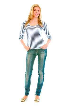 Full length portrait of smiling beautiful teen girl with hands in pockets of jeans  isolated on white  photo