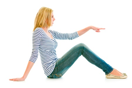 Beautiful teen girl sitting on floor and pointing finger at copy-space isolated on white