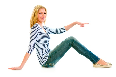 copys pace: Smiling beautiful teen girl sitting on floor and pointing finger at something isolated on white