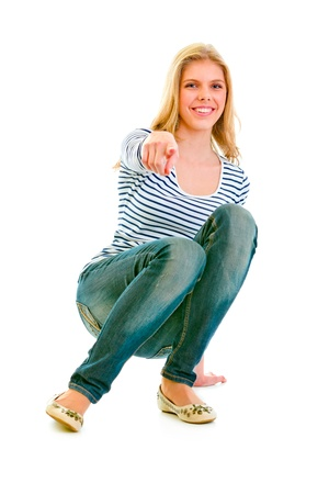 Smiling beautiful teen girl squatting and pointing finger at you isolated on white  photo