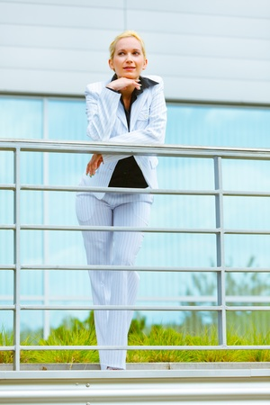 Portrait of smiling modern business woman leaning on railing at office building   photo