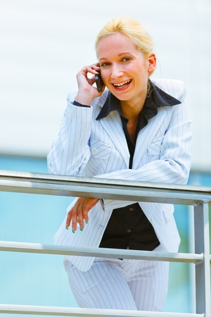 Smiling modern business woman leaning on railing at office building and talking on mobile  photo
