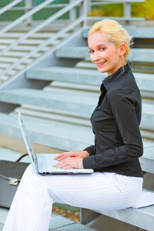 Smiling modern business woman sitting on stairs at office building and working on laptop  photo