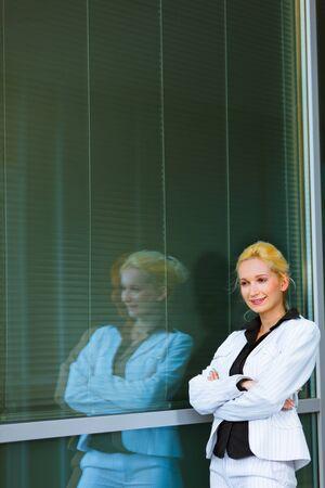 Pensive modern business woman standing near office building   photo