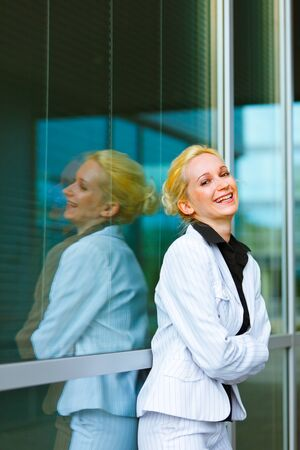 Laughing modern business woman with crossed arms on chest at office building   photo