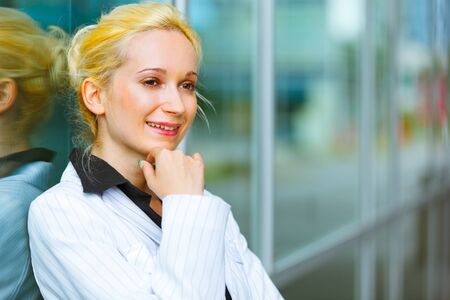 sagacious: Pensive modern business woman with hand near face standing near office building