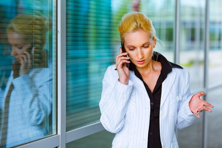 Concentrated modern business woman talking on mobile at office building   photo
