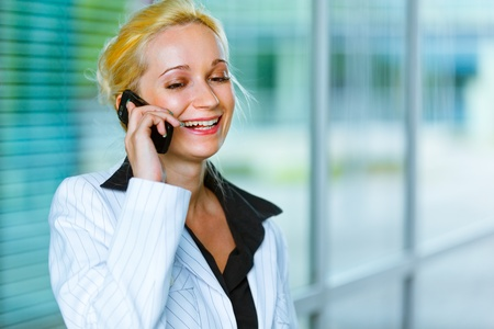 Smiling modern business woman talking on mobile at office building   photo