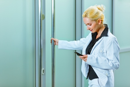 Smiling modern business woman with mobile entering office building   photo