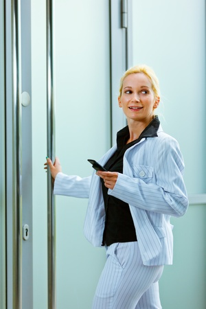 Smiling modern business woman entering office building holding mobile in hand  photo