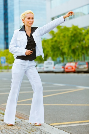 Smiling modern business woman catching taxi near office center  photo