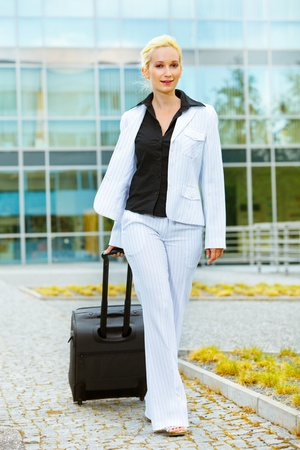 Travelling smiling modern business woman with suitcase   photo