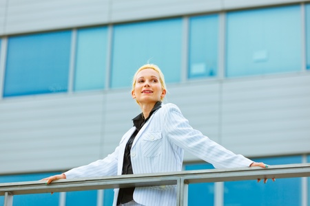 Smiling modern business woman leaning on railing at office building looking at copyspace   photo