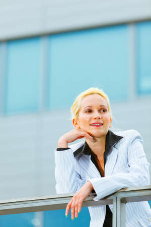 Thinking about something modern business woman leaning on railing at office building   photo
