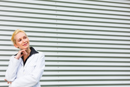 Smiling modern business woman standing at office building and looking at copyspace   photo