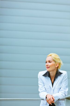 Thoughtful modern business woman leaning on railing at office building and looking at copyspace   photo