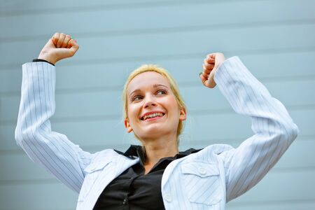 Excited modern business woman standing at office building  and rejoicing her success   photo