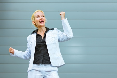 Pleased modern business woman standing at office building  and rejoicing her success   photo