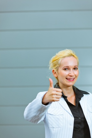 Standing at office building modern business woman showing thumbs up gesture Stock Photo - 9950903