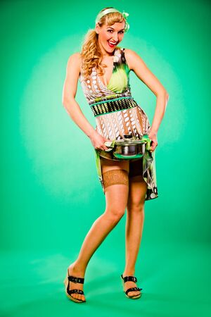 Smiling beautiful woman holding hot casserole in hands. Pin up and retro style.  photo