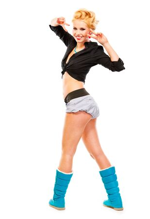 Full length portrait of standing in half-turn smiling girl showing victory gesture isolated on white photo