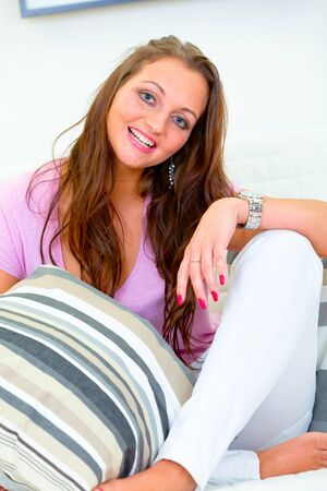 divan: Smiling beautiful young woman relaxing on white divan at home
