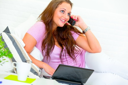 Happy pretty housewife on sofa at home talking on phone and using laptop