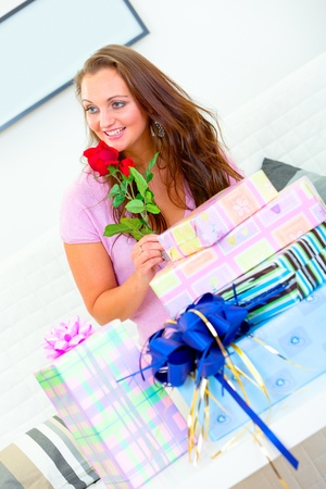 Smiling pretty woman sitting among gifts at home and holding rose