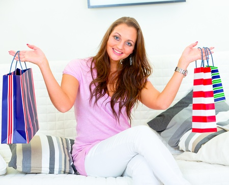 Cheerful lovely woman sitting on sofa at home and holding shopping bags in hands  photo