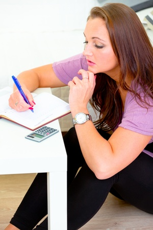 sagacious: Pensive lovely woman sitting on floor at home and making notes in diary  Stock Photo
