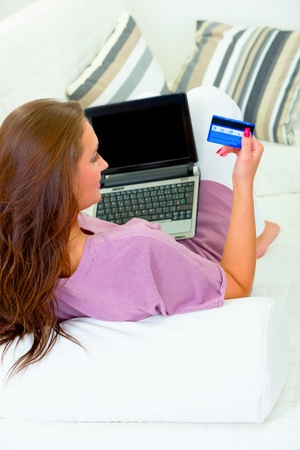 Woman sitting on sofa at home with laptop and credit card
