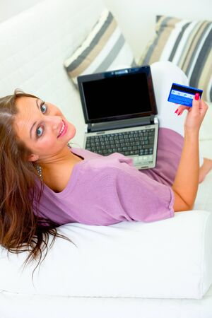 Smiling modern housewife sitting on sofa at home with laptop and credit card