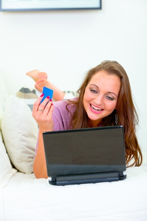 Cheerful beautiful woman lying on sofa at home and using credit card to shop from net