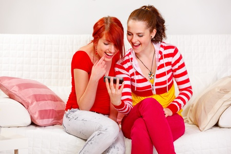 Happy girl showing mobile to her smiling girlfriend  at living room   photo