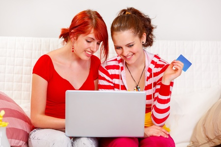 Two happy girlfriends making purchase using credit card  at living room   photo
