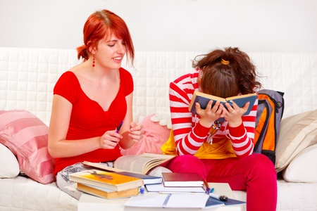 classbook: Caring girl helping study her tired girlfriend at living room   Stock Photo