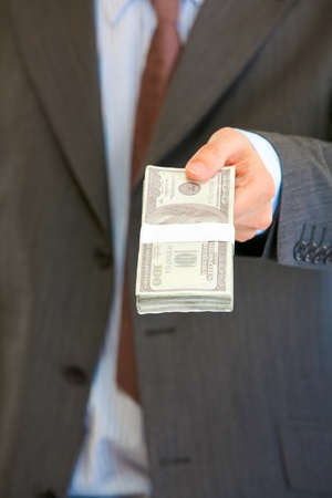 batch of dollars: Businessman giving stack of dollars. Close up.  Stock Photo