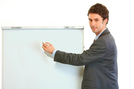 Smiling modern businessman giving presentation using flipchart  isolated on white  Stock Photo