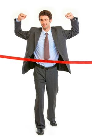 Full length portrait of pleased businessman  crossing finish line isolated on white. Concept - success achievement  photo