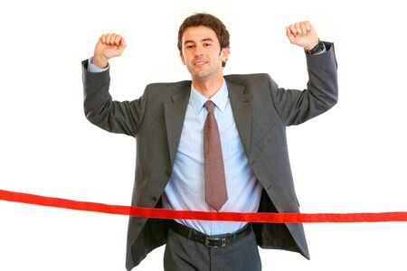 Pleased businessman  crossing finish line isolated on white. Concept - success achievement  photo