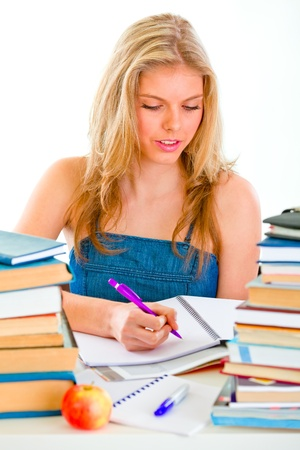 Young girl sitting at table with lots of books and doing homework  photo