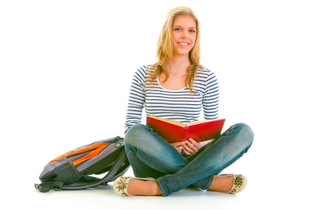 schoolbook: Smiling teen girl with backpack sitting on floor and reading schoolbook isolated on white