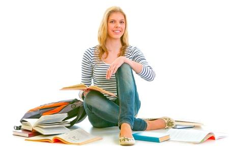 Cheerful teen girl sitting on floor among schoolbooks isolated on white Stock Photo - 10344784