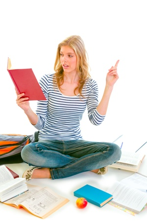 Pensive teenager sitting on floor among schoolbooks and studying isolated on white   photo