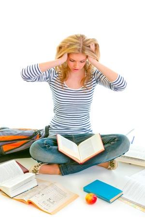 Teen girl sitting on floor among schoolbooks and studying hard isolated on white Stock Photo - 10344815