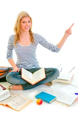 classbook: Smiling teen girl sitting on floor among schoolbooks and pointing in corner isolated on white   Stock Photo
