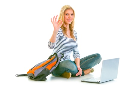 Girl sitting on floor with backpack and laptop showing ok gesture isolated on white   photo
