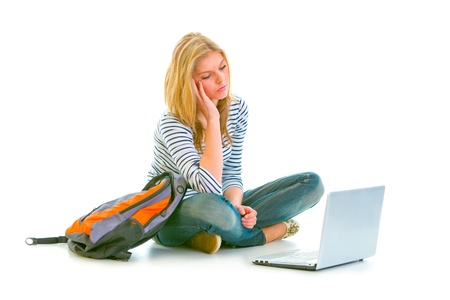 Tired teen girl sitting on floor with backpack and looking on laptop isolated on white   photo