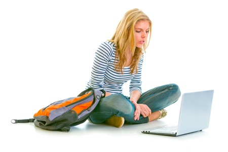 interrogatively: Interested pretty girl sitting on floor with backpack and looking on laptop isolated on white
