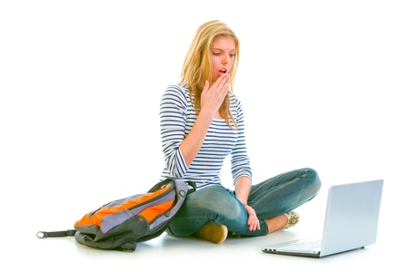 Amazed teen girl sitting on floor with backpack and looking on laptop isolated on white 